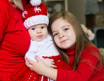 Face, Christmas hat, red suit, hands mother, fun. Beautiful little blonde baby girls, has happy fun cheerful smiling face, blue eyes, has red Christmas hat Santa Royalty Free Stock Photo