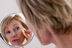 Face Cleaning. Mature beautiful Woman Cleaning Face Stock Photos