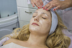 Face cleaning. Young woman having treatment receiving therapy with ultrawave skin care instrument. closeup portrait with hands of doctor Stock Photos