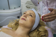 Face cleaning. Young woman having treatment receiving therapy with ultrawave skin care instrument. closeup portrait with hands of doctor Royalty Free Stock Image