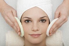 Face Cleansing. Young woman receiving face cleansing at beauty spa Stock Photo