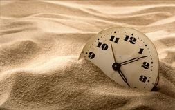 Face of clock in sand Stock Photos