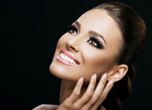 Face close-up of a beautiful young woman isolated on dark background; perfect skin, beauty portrait Stock Photo