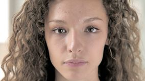 Face close up of serious curly hair woman stock footage