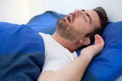 Man in bed suffering for sleep apnea syndrome royalty free stock image