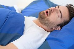 Man in bed suffering for sleep apnea syndrome Stock Photo