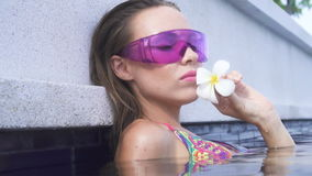 Face closeup of young woman wearing bikini and purple sunglasses with white flower looking at camera in infinity rooftop pool