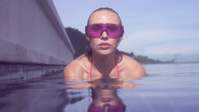 Face closeup of young woman wearing purple sunglasses looking at camera in infinity rooftop swimming pool on a sunny day. Face closeup of young woman wearing stock footage