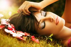 Face closeup of woman with beauty make-up outdoor. On green grass and flower petals royalty free stock photo