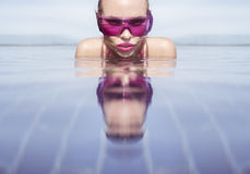 Face closeup of woman in purple sunglasses in infinity rooftop swimming pool Royalty Free Stock Photos