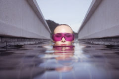 Face closeup of woman in purple sunglasses in infinity rooftop swimming pool Royalty Free Stock Photography