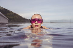 Face closeup of woman in purple sunglasses in infinity rooftop swimming pool Stock Image