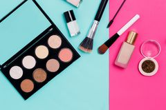 Face concealer, nail Polish, brush, Foundation, eyeshadow and glitter and smartphone on colorful pink and blue background, top stock photography