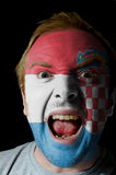 Face of crazy angry man painted in colors of Croatia flag. Low key portrait of an angry man whose face is painted in colors of croatian flag Royalty Free Stock Photography