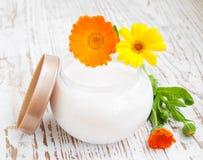 Face cream and calendula flowers Stock Photos