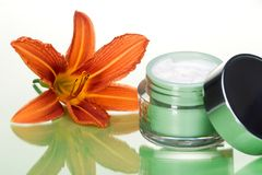 Face cream and flower. Closeup of container of opened moisturizing face cream and blooming lily on green toned background Royalty Free Stock Images
