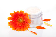 Face cream and gerbera flowers Stock Photos