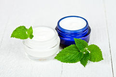 Face cream in jars with urtica leaves Royalty Free Stock Photography