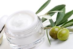 Face cream and olive twig. Closeup of jar of moisturizing face cream and twig with green olives Royalty Free Stock Photography
