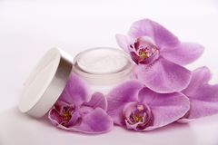 Face cream and purple orchid flower Royalty Free Stock Photography