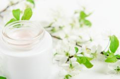 Face cream in white jar on a white background with white small flowers of an apple tree. Concept natural cosmetics stock images