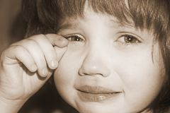 The face of a crying girl, wiping tears, Sepia stock photography