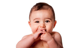 Face of a cute baby infant. Beautiful Face of a happy cute baby infant with hands in mouth, isolated stock photo