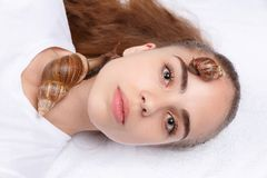 Face of girl close-up with two snails on white background Royalty Free Stock Photography