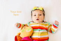 Face of cute surprised baby infant girl in colored pajamas with a bow on her head, making funny mouth expression. Copy Royalty Free Stock Photography
