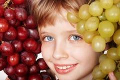 Face da menina da criança com uvas. Fotografia de Stock Royalty Free