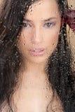 Face da mulher atrás de de vidro completamente de gotas da água Imagem de Stock Royalty Free