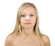 Face da mulher nova com emplastro de colagem no nariz fotografia de stock royalty free
