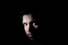 A face in darkness. Portrait of an Indian man in the darkness Stock Photography