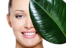 Face de riso feliz da mulher e da grande folha verde Fotografia de Stock