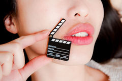 Face detail of sensual woman lips with little clapper board. Face detail of sensual woman lips, no eyes, with hand holding little movie clapper board Stock Photography
