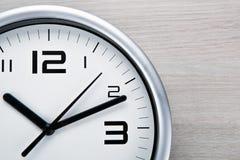 Face do relógio branca com dígitos pretos em um fundo cinzento de madeira imagens de stock royalty free
