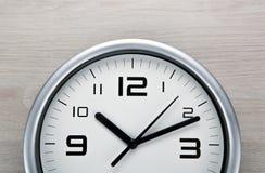 Face do relógio branca com dígitos pretos em um fundo cinzento de madeira fotos de stock royalty free