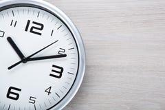 Face do relógio branca com dígitos pretos em um fundo cinzento de madeira imagem de stock royalty free
