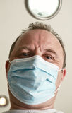 Face of the doctor in a mask closeup . Doctor wearing a face mask on   white background Royalty Free Stock Images