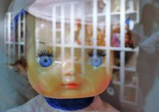 A face of a doll seen through the glass window.