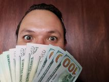 Face with emotion expression of a young man and American banknotes. Face with emotion expression of a young man and holding american banknotes. commerce stock photos