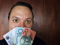 Face with emotion expression of a young man and Australian banknotes. Commerce, exchange, trade, trading, value, buy, sell, profit, price, rate, cash, currency stock images