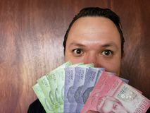 Face with emotion expression of a young man with chilean banknotes. Commerce, exchange, trade, trading, value, buy, sell, profit, price, rate, cash, currency royalty free stock photos