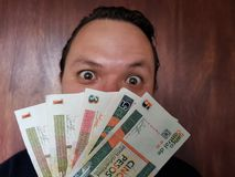 face with emotion expression of a young man and cuban banknotes stock photos