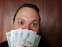 Face with emotion expression of a young man with guatemalan banknotes. Commerce, exchange, trade, trading, value, buy, sell, profit, price, rate, cash royalty free stock photos