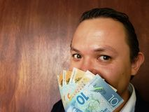 Face with emotion expression of a young man with New Zealand banknotes. Commerce, exchange, trade, trading, value, buy, sell, profit, price, rate, cash royalty free stock photos