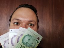 face with emotion expression of a young man and singaporean banknotes stock photo
