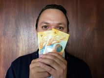 Face with emotion expression of a young man with swiss banknotes. Commerce, exchange, trade, trading, value, buy, sell, profit, price, rate, cash, currency royalty free stock photo