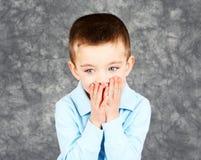 Face escondendo do menino novo nas mãos Imagem de Stock Royalty Free