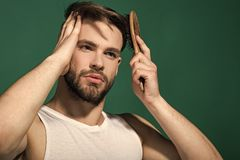 Face fashion boy or Man in your web site. Man face portrait in your advertisnent. Haircare, hairstyle concept. Man brush hair with hairbrush on green stock images